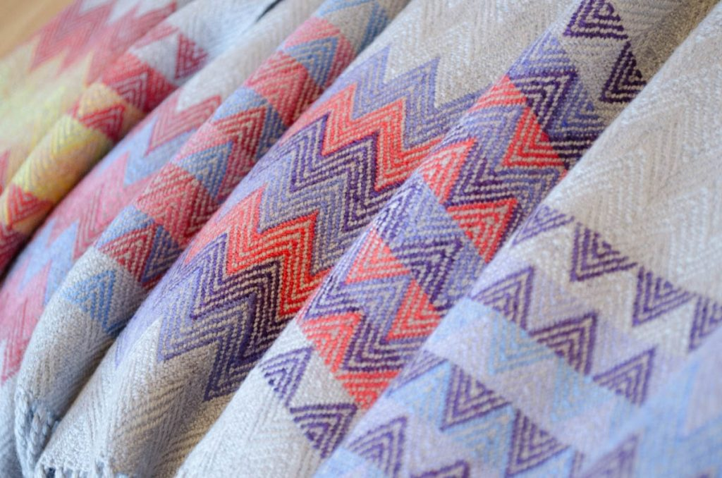 Close-up of several pale grey scarves with differently coloured zig-zag patterns at the ends.