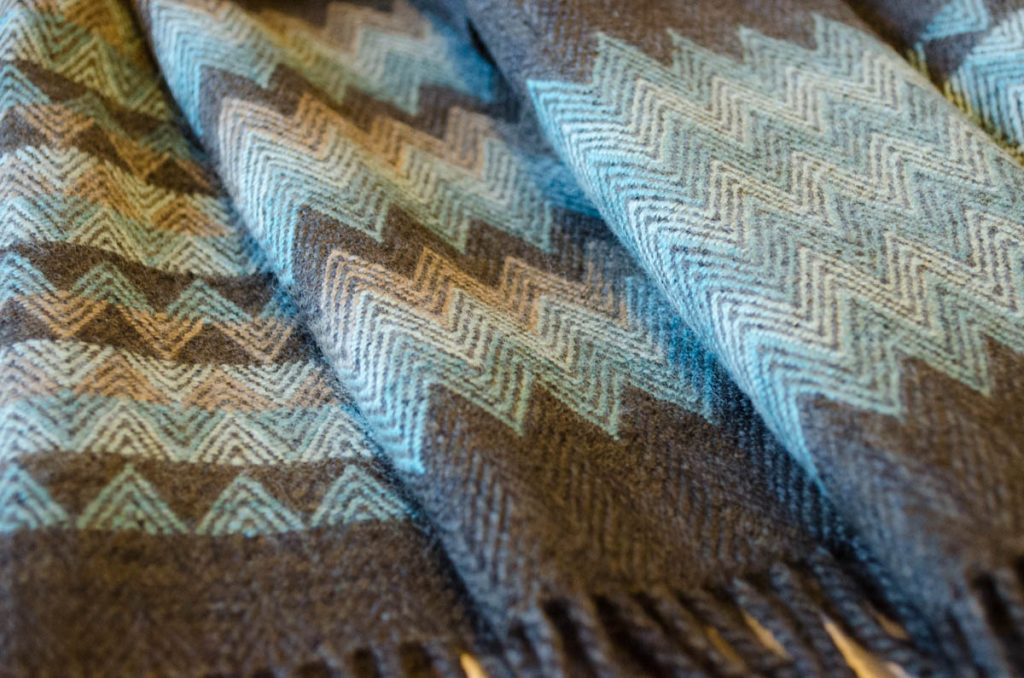 Close-up of dark brown scarves showing front and reverse side of patterning in mint-green and light coffee-brown.
