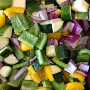 Chopped vegetables including green and yellow peppers, red onions, courgettes