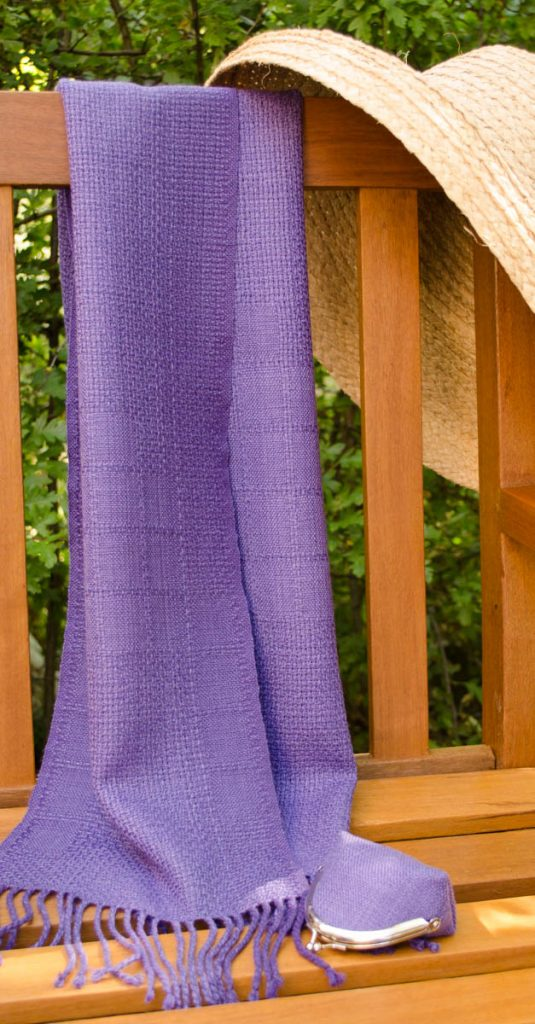 Purple lace scarf draped over a garden bench.