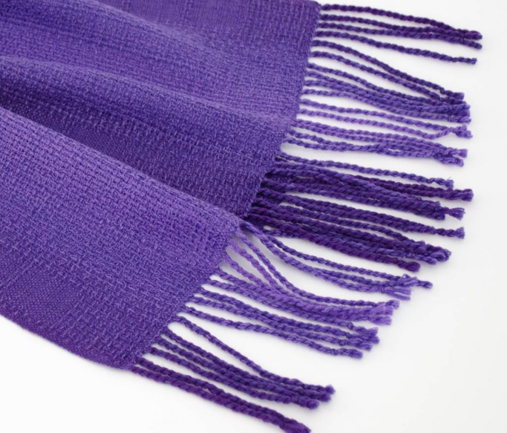 One end of a purple lace scarf showing the fringe laid out on a plain white surface.