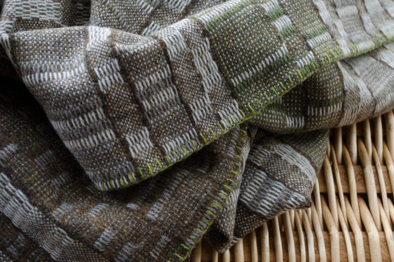 A rumpled wool blanket lies on top of a wicker surface. The edge of the fabric is hand-stitched with blanket stitch.