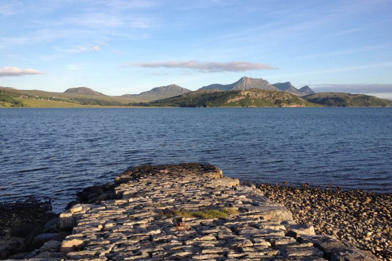 View of a cobbled slipway leading into a shallow sea loch. There is a line of hills in the background under a blue sky.