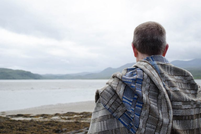 A man looks out over the same sea loch, but under a cloudy sky. He is wrapped in a handwoven wool blanket.