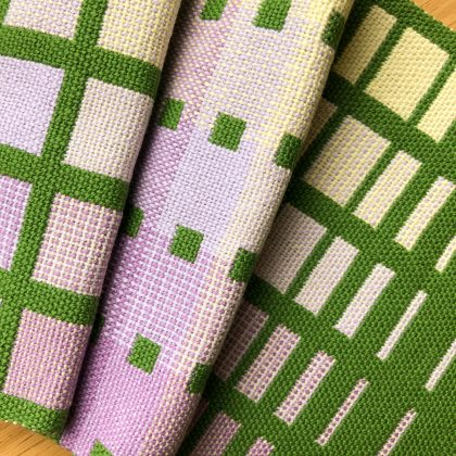 Folded double weave fabric woven in green, lavender and lemon. Blocks of different sizes and colours are shown.